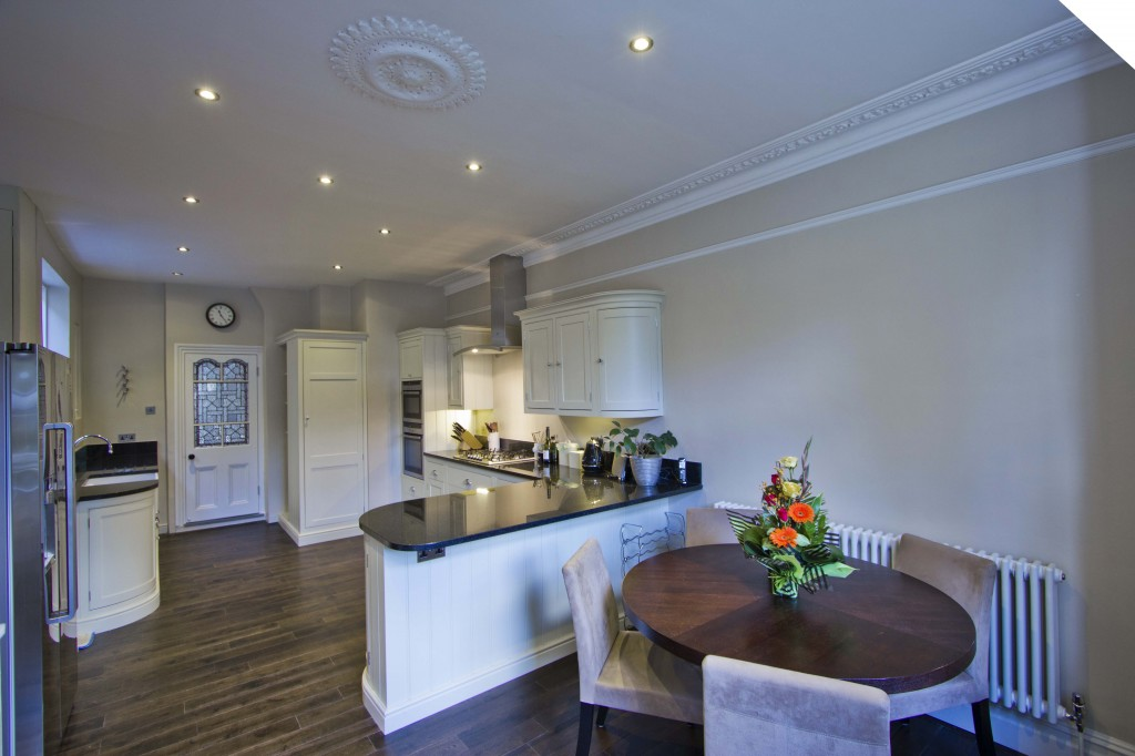 Dining Room in white with dark wood flooring and marble worktops.