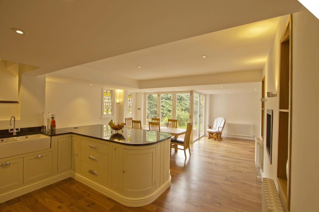 Looking across open plan kitchen into dining room with french windows