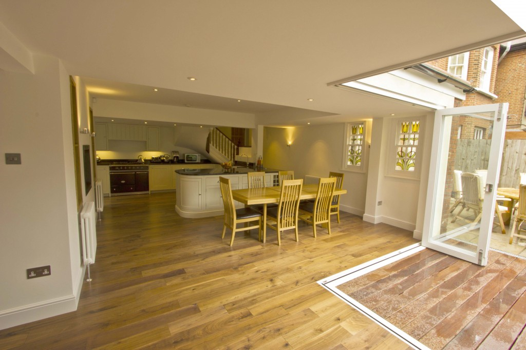 Looking across open plan dining room with wooden floor towards kitchen.